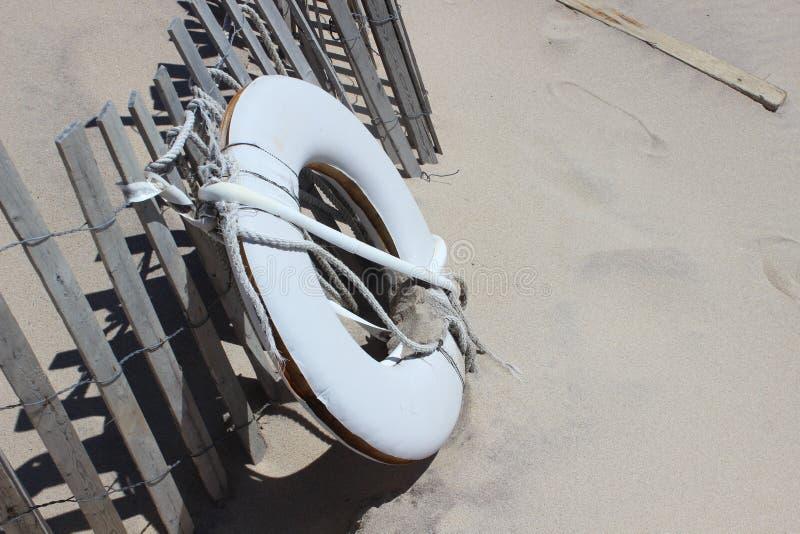 Белый спасательный жилет на песочном прибрежном пляже океана стоковая фотография