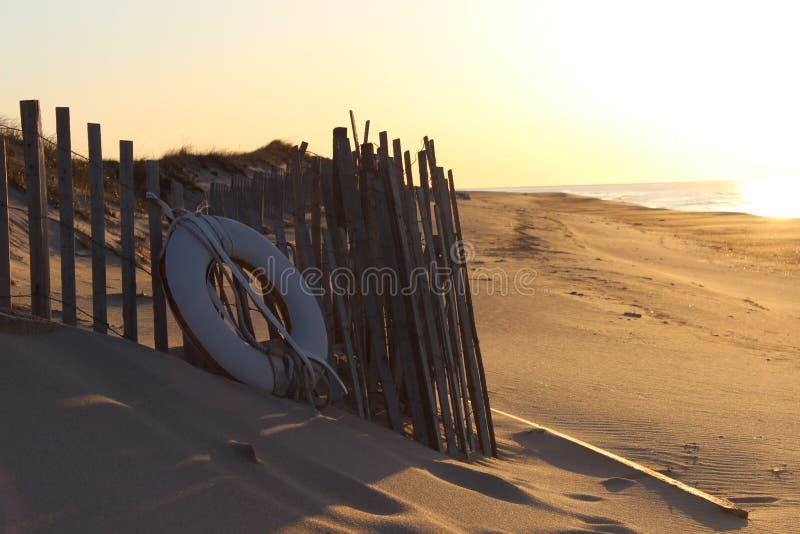Белый спасательный жилет на песочном прибрежном пляже океана стоковая фотография rf