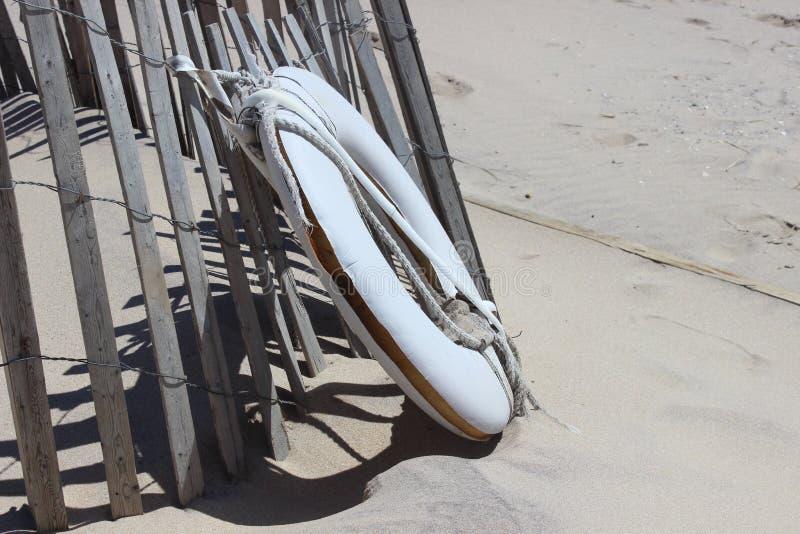 Белый спасательный жилет на песочном прибрежном пляже океана стоковое фото