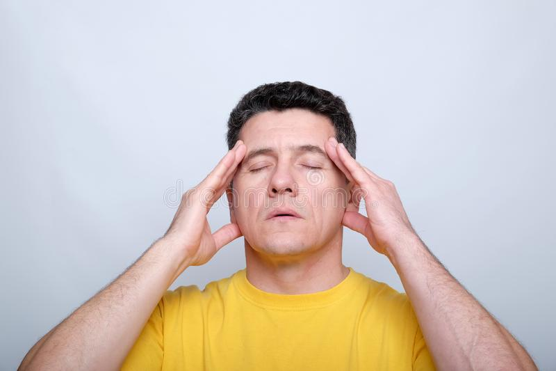 Белый средн-достигший возраста человек с закрытыми глазами касаясь его голове с 2 руками стоковое фото rf