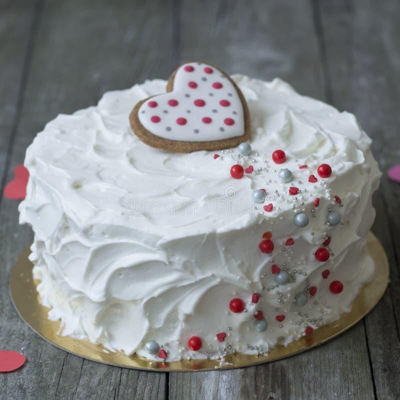 Белый торт украшенный с печеньями в форме сердец и шлихтой кондитерскаи на старой деревянной предпосылке красный цвет поднял стоковая фотография rf