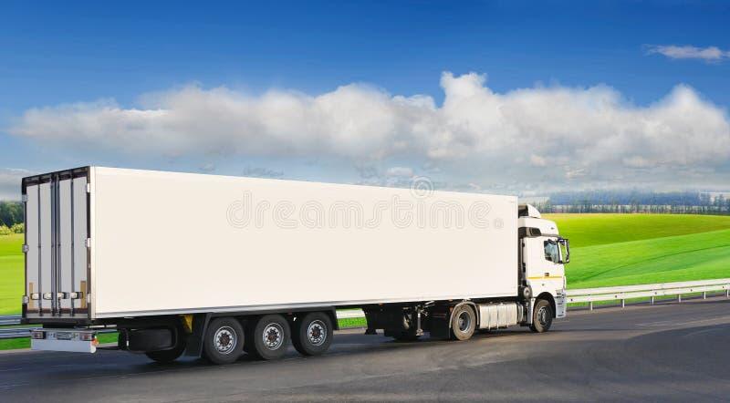Белый трейлер на шоссе, на фоне зеленого поля стоковые фото