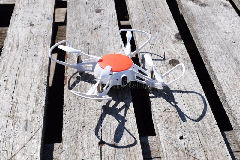 Белый трутень на деревянной предпосылке Технология в aero стрельбе фото стоковое фото rf