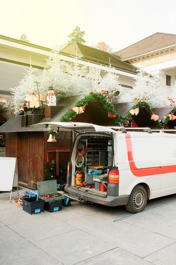 Белый фургон при разнообразные инструменты устанавливая рождественскую ярмарку стоковые фото
