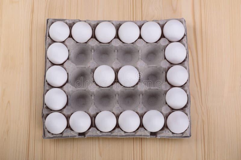 Белый цыпленок eggs в картонной коробке с пустыми космосами, backgro стоковые фотографии rf