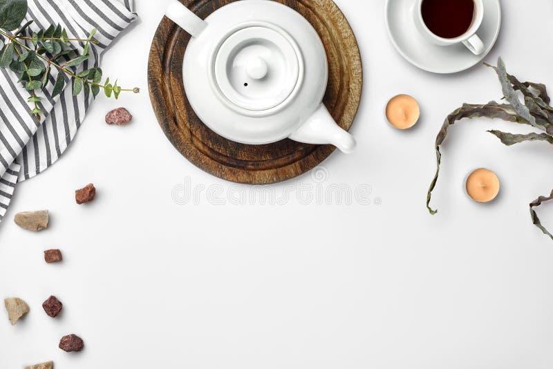 Белый чайник фарфора на деревянной доске и белой чашке с чаем на таблице Взгляд сверху скопируйте космос стоковая фотография