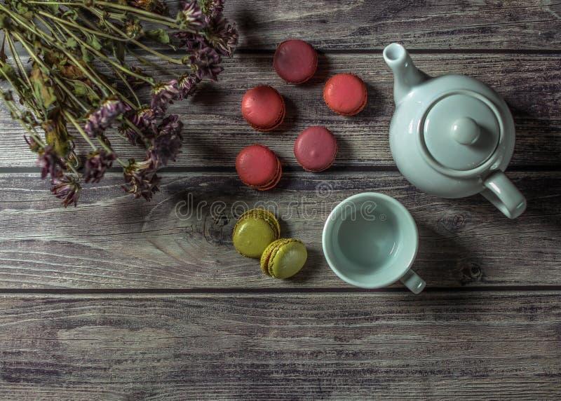 Белый чайник, чашка, букет цветков поля и красочные macaroons на деревянном столе стоковое изображение