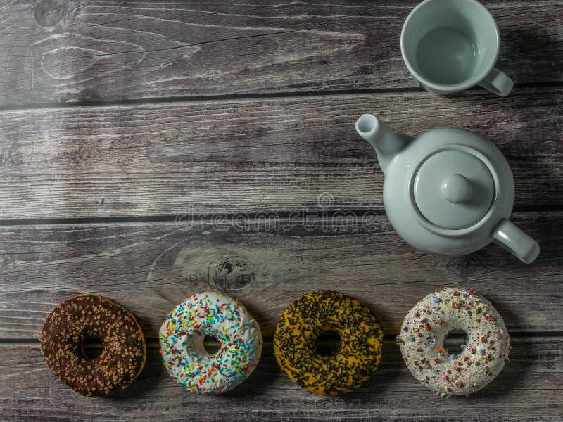 Белый чайник, чашка и красочные donuts на деревянном столе Время чая на сладком доме стоковые фотографии rf