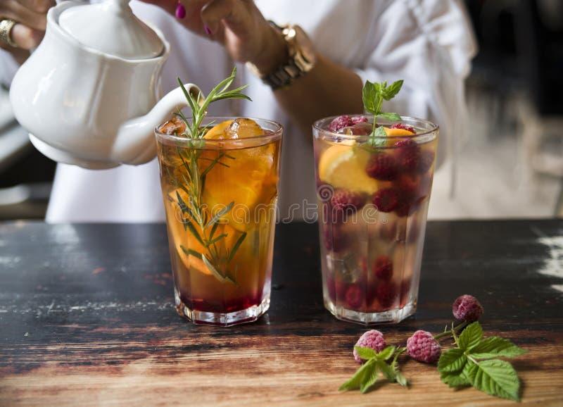 Белый чай с сиропом, апельсином, поленикой, розмариновым маслом и мятой на деревенской предпосылке стоковое фото rf