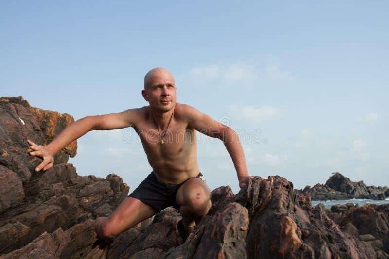 Белый человек взобранный к верхней части скалы Он сильн и счастлив стоковое фото