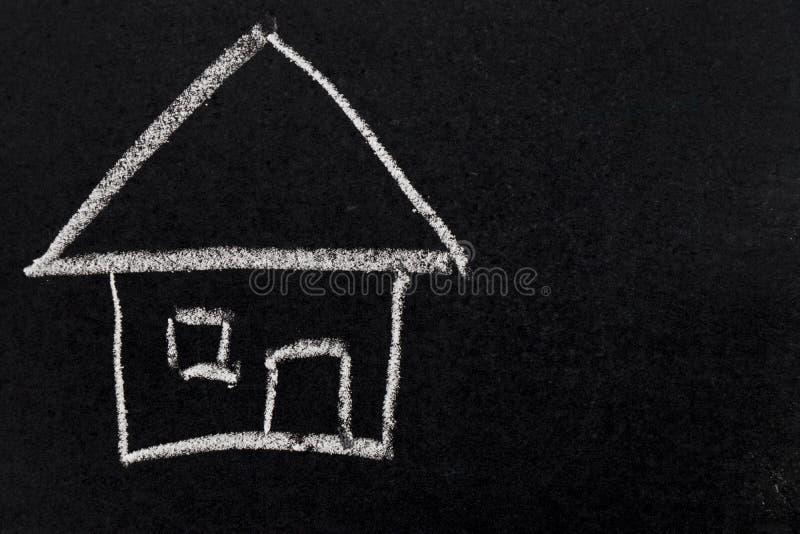 Белый чертеж мела как форма дома на черной доске стоковые изображения rf