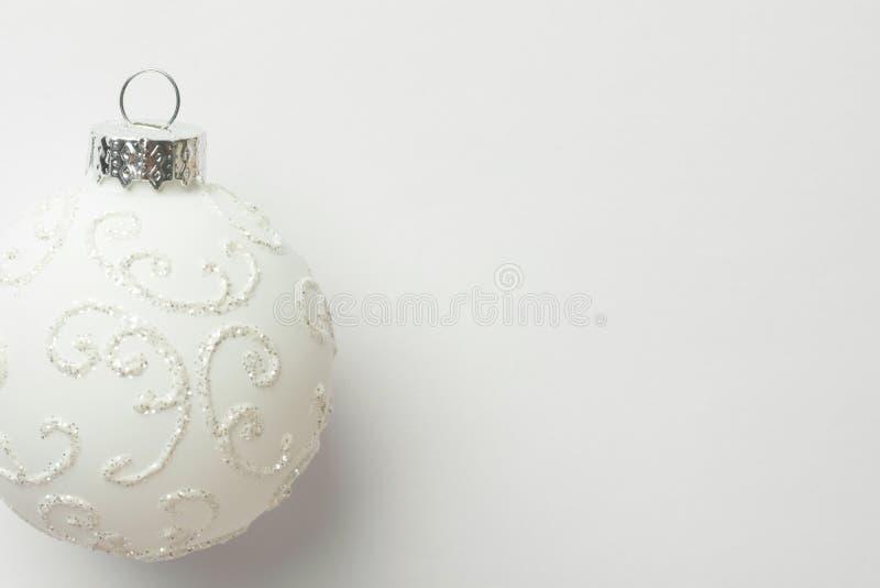 Белый шарик рождественской елки орнамента на такой же предпосылке monochrome цвета Плакат поздравительной открытки Нового Года в  стоковые изображения rf