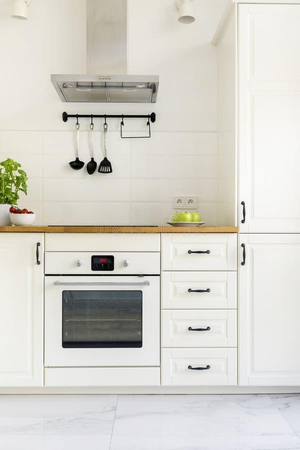 Белый шкаф в минимальном интерьере кухни с деревянным countertop стоковые фото