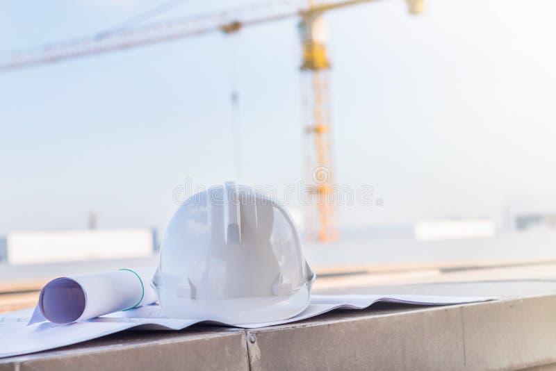 Белый шлем безопасности и светокопия на строительной площадке w стоковые изображения