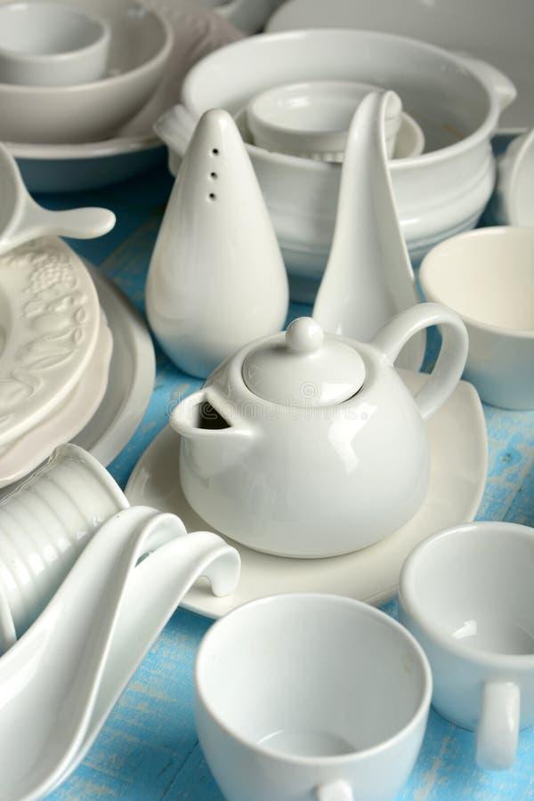 Белый kitchenware фарфора на свете - голубом деревянном столе стоковое фото rf