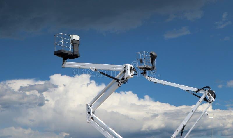 2 белых автотелескопической вышки против голубого неба с облаками, вниз там пушистые облака, над темными облаками стоковое изображение rf