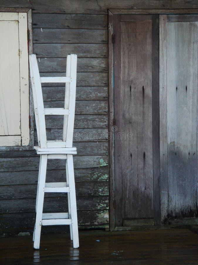 2 белых стуль табуретки перед коричневой деревянной стеной стоковое фото rf