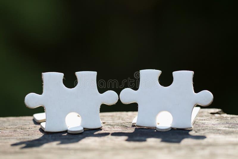 2 белых части стойки головоломки на деревянном столе изолированном на черной предпосылке, концепции соединяться стоковая фотография rf