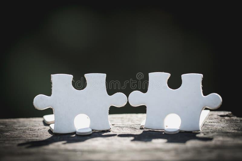 2 белых части стойки головоломки на деревянном столе изолированном на черной предпосылке, концепции соединяться стоковое изображение rf
