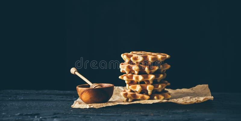 Бельгийский waffle и шар меда на темном деревянном столе стоковое изображение rf