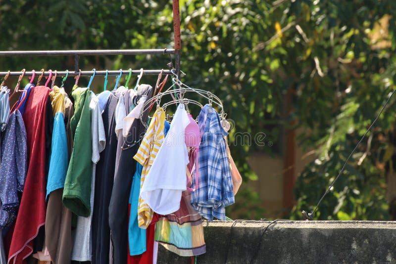 Бельевая веревка, внешний солнечный свет outdoors, одежды вида запускает день в сельской местности Цвета одежды в одеждах стоковое фото rf