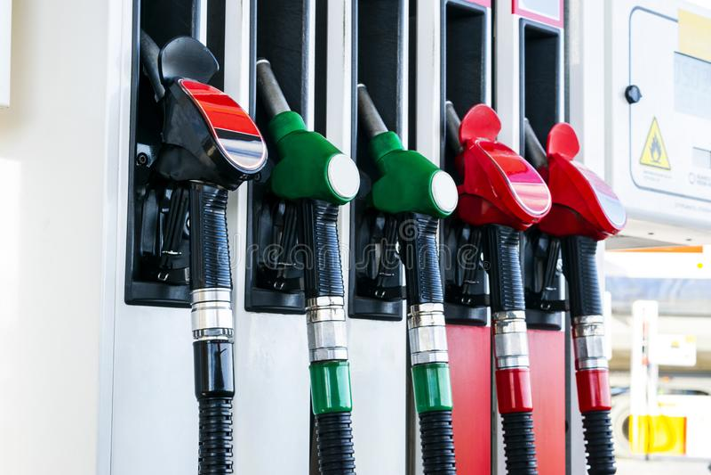 Бензин и тепловозный раздатчик на бензоколонке Сопла газового насоса Конец-вверх оружия нефти заполняя на бензоколонке Цветастый  стоковые фото