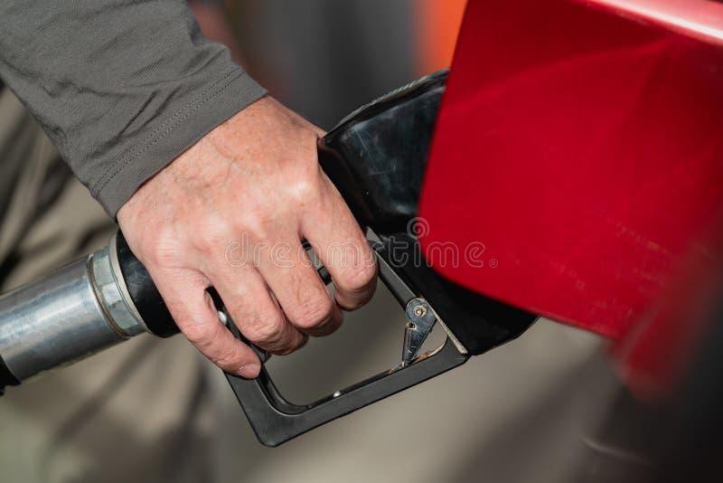 Бензоколонка, сопло газового насоса, старшая рука человека стоковые фотографии rf