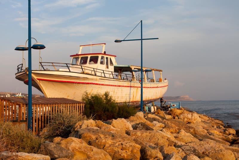 Берег Средиземного моря в Кипре с старой шлюпкой стоковые изображения