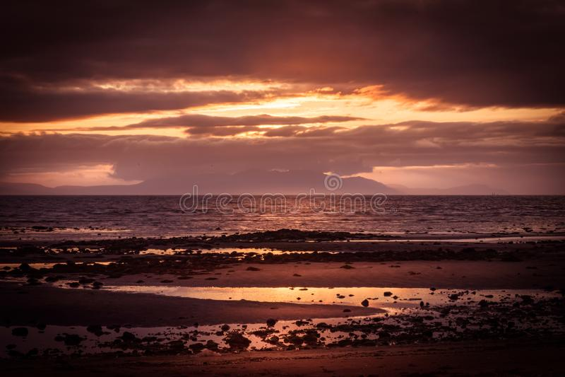 Берег Трун Barassie в Ayrshire Шотландии с красным унылым небом стоковые фотографии rf