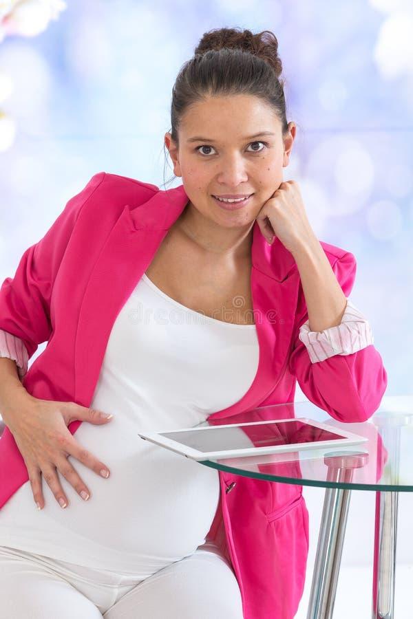 Беременная азиатская женщина работая в офисе стоковая фотография