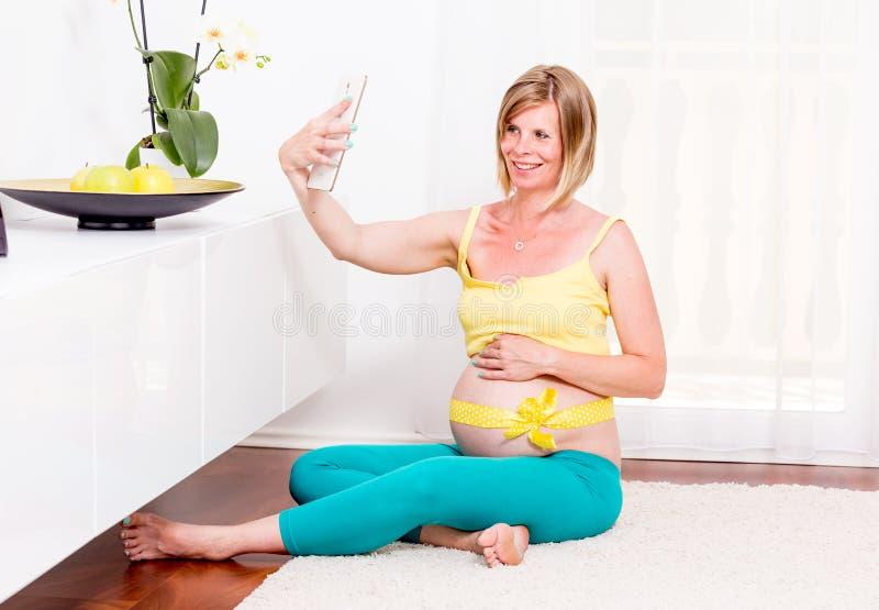 Беременная белокурая женщина в ее доме стоковая фотография