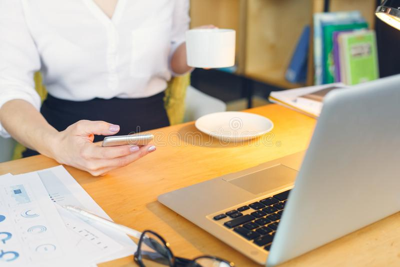 Беременная бизнес-леди работая на материнстве офиса сидя держащ smartphone стоковые фото