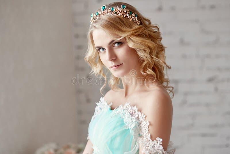 Беременная блондинка невесты подготавливает стать матерью и женой Длинное платье бирюзы на теле девушки Вьющиеся волосы и красиво стоковое изображение