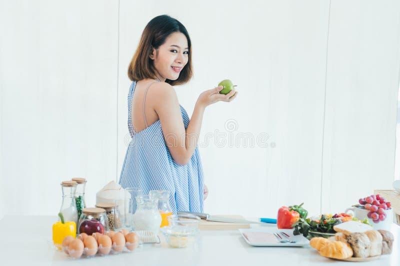 Беременная девушка Азии красивая держит зеленое яблоко стоковые фотографии rf