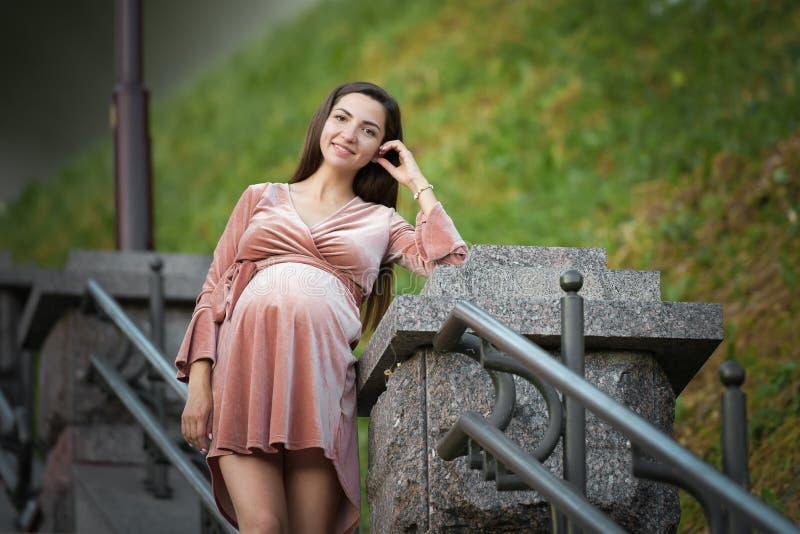 Беременная девушка в бежевом платье Беременная девушка брюнета в бежевом платье В ожидании ребенка Будущая мама стоковые изображения rf