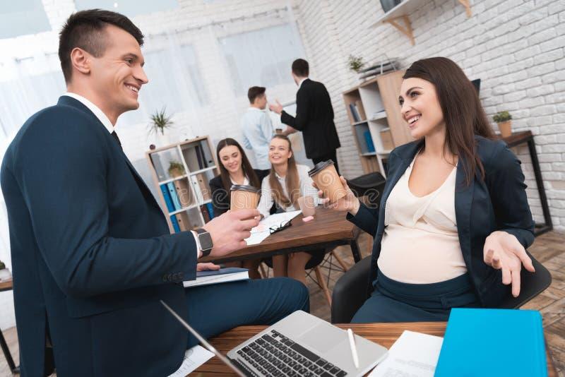 Беременная девушка в офисе выпивает кофе с вождем в офисе Беременная с коллегами стоковые фотографии rf