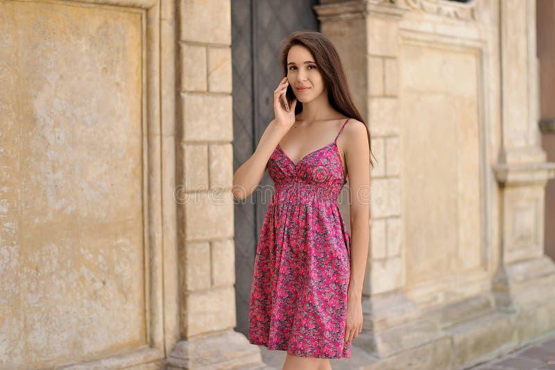 Беременная девушка говорит телефоном на предпосылке города стоковые изображения