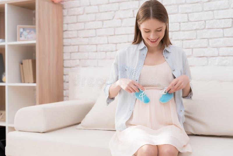 Беременная девушка держит ботинки для newborn стоковое изображение