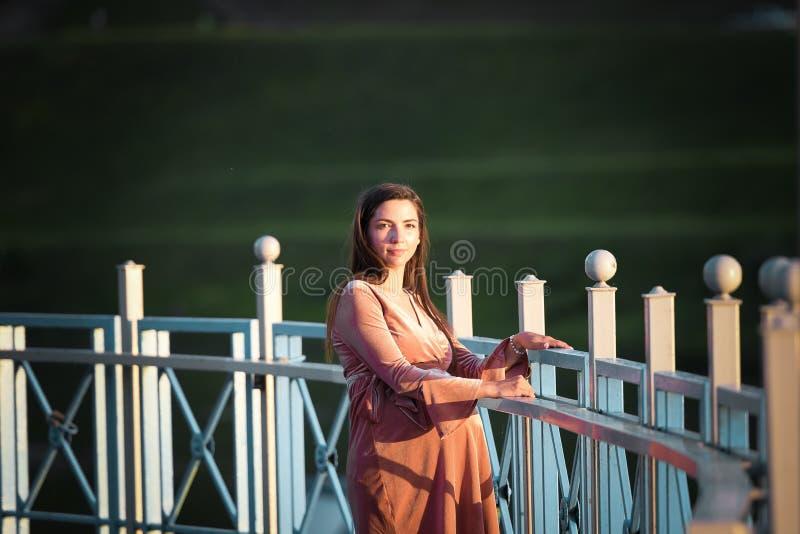 Беременная девушка идя вдоль прогулки Портрет девушки с животом Маленькая девочка в платье лета идя вдоль стоковые фотографии rf