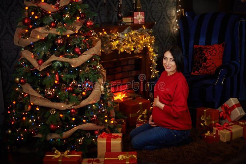 Беременная девушка одевает рождественскую елку стоковое фото