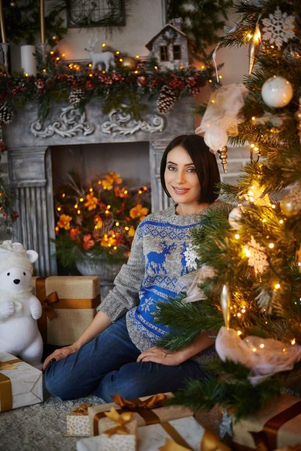 Беременная девушка сидя с настоящими моментами на рождественской елке стоковое изображение rf