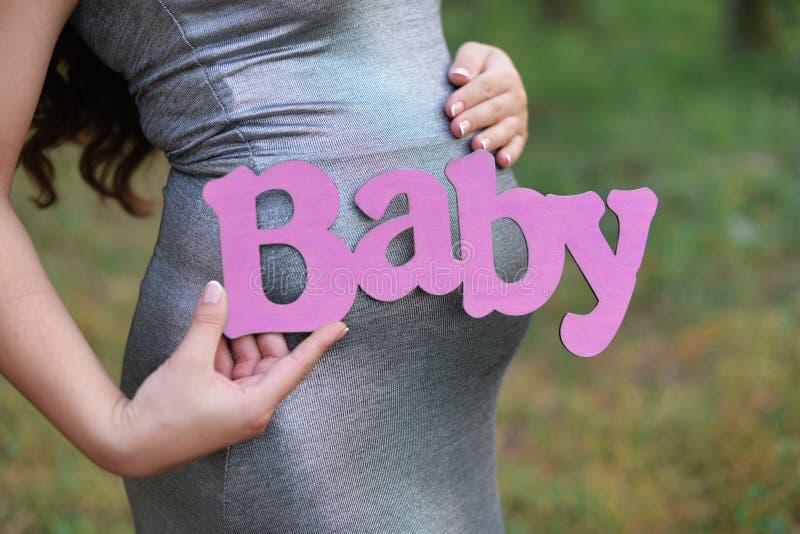 Беременная девушка с животом ждать с пинком письма надписи писем стоковое фото