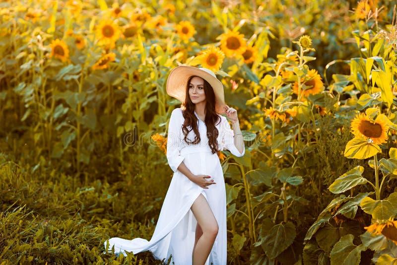 Беременная европейская женщина в поле солнцецветов, красивая молодая европейская женщина ждать ребенка, prenant женщины с стоковое фото rf