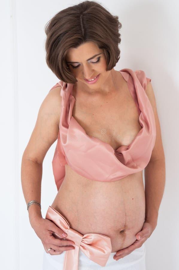 Беременная девушка с розовым смычком стоковая фотография