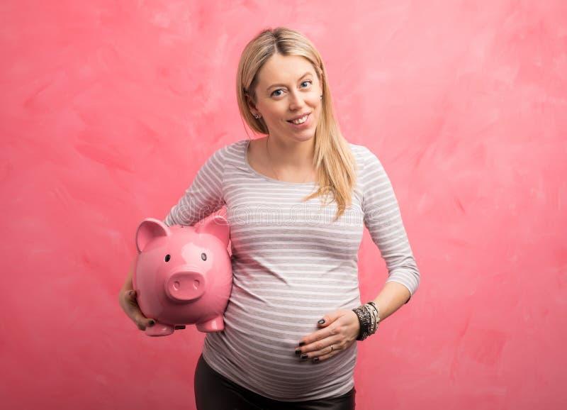 беременная женщина банка piggy стоковая фотография