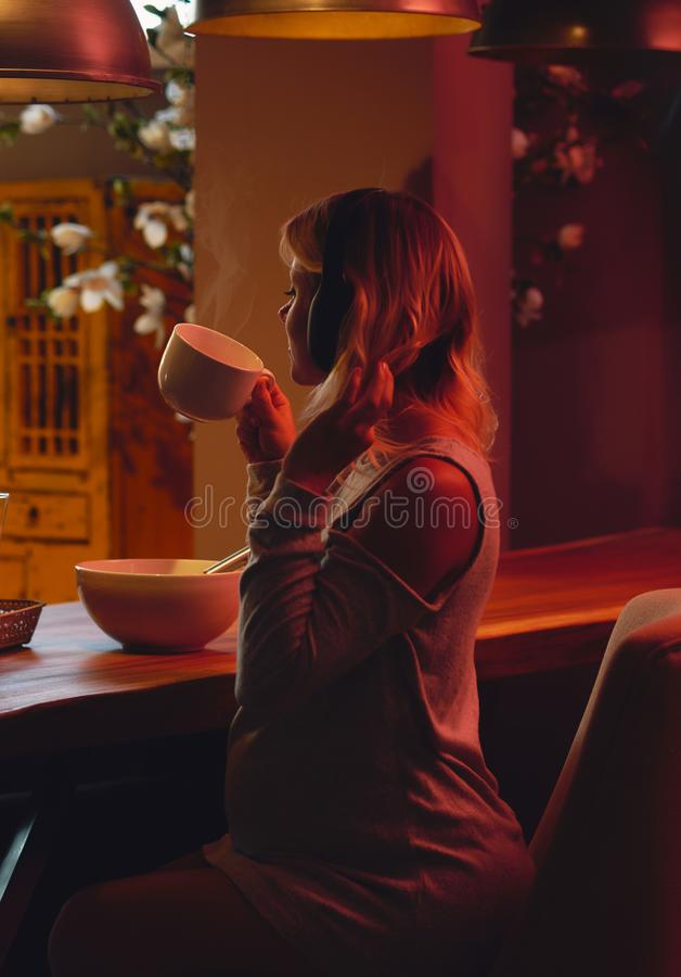 Беременная женщина выпивая музыку чая и listenig дома стоковое фото