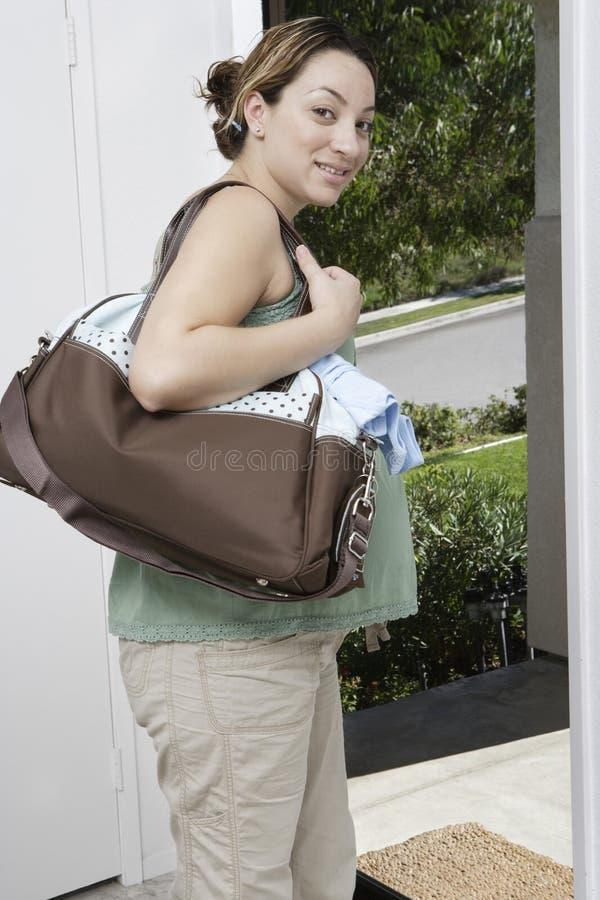 Беременная женщина выходя домой стоковые изображения