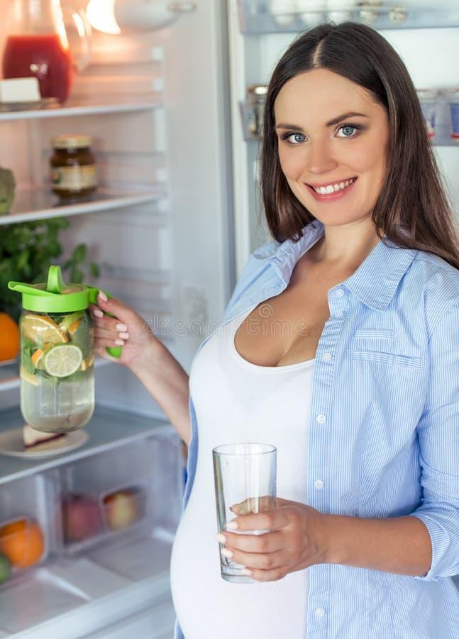 Беременная женщина в кухне стоковые фото
