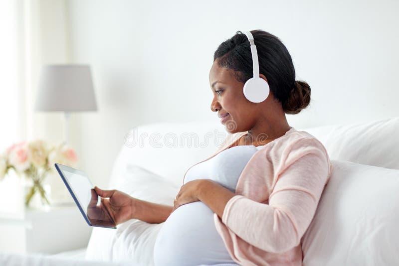 Беременная женщина в наушниках с ПК таблетки стоковые изображения rf