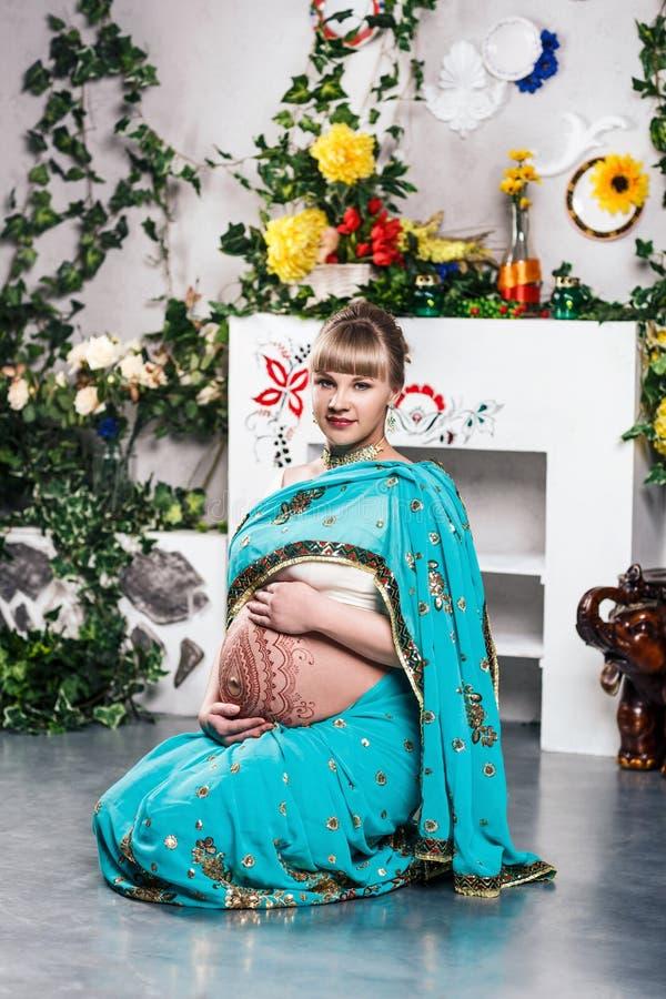 Беременная женщина в сари с татуировками хны стоковое изображение